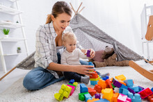 Young Mother Playing With Construction Blocks With Son On Floor Near Kids Wigwam