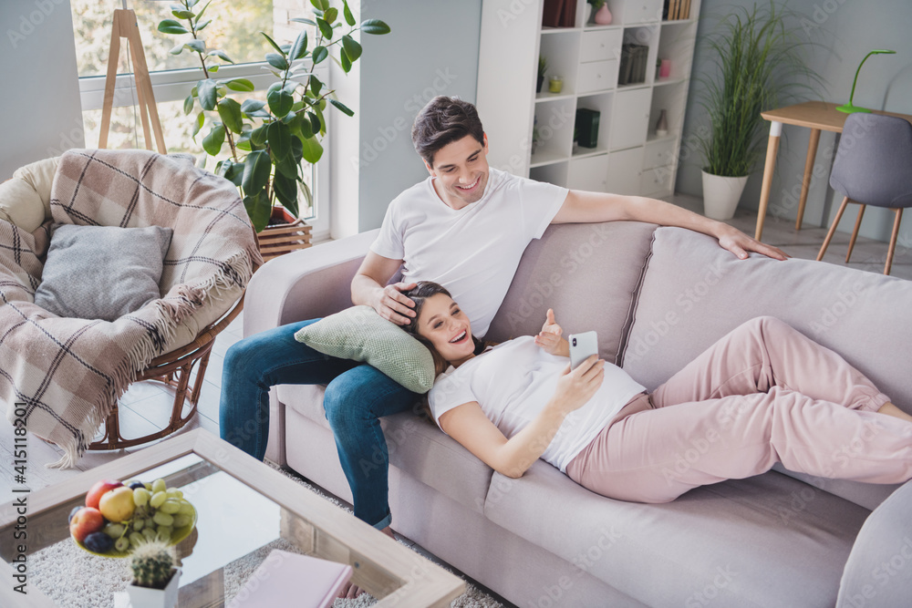 Fototapeta Full size photo of happy young family sit lie sofa hold phone browsing parenthood on weekend in house indoors