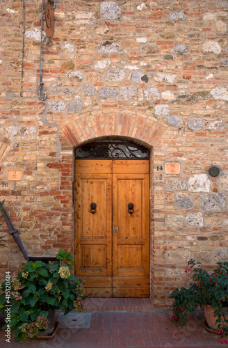 Fototapeta premium Sienna, Tuscany, Italy - Wooden doors in a brick and stone building.