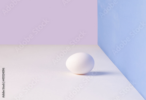 Fototapeta White single egg. Chicken egg with soft shadows on white table. pink, blue background. Template for Easter holiday. obraz na płótnie
