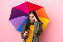 Young Woman Holding An Umbrella Isolated On Pink Background Laughing