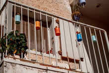 Multicolored Metal Flower Pots Are Hung From The Iron Bars Of The Balcony