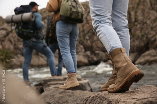 Group of friends with backpacks crossing mountain river, focus on hiking boots Fototapet