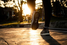 The Concept Of Jogging, Legs And Feet Are In The Stride And Run Or Walk In Orange Tones In The Sunset.