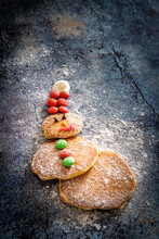 Home Made Pancakes In Shape Of Snowman Decorated With Sugar Buttons On Table Background At Christmas Time
