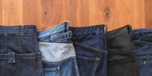 Variety Of Jeans And Denim Pants On Wooden Table With Copyspace 様々な色や形のジーンズ・ジーパン・デニムパンツ 木製テーブル コピースペース