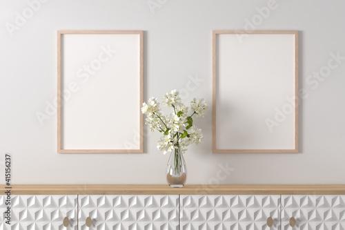 Obraz na plátne Interior design - sideboard with a glass vase of geranium flowers