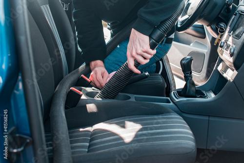 Obraz na plátně Detalle de un hombre limpiando el interior de un automóvil con una aspiradora pr