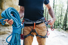 Close-up Of A Strong Climber With Equipment On A Belt Holding Rope And Preparing To Climb