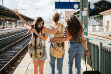 Three Young Beautiful Female Women At Station To Catch Train For Their Vacation Together During Coronavirus Covid-19 Pandemic Wearing Protective Face Masks - Millennials Have Fun During The Holidays