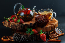 Glass Teapot. Still Life With Hot Tea With Lemon And Strawberries. Wooden Stand. Splash.