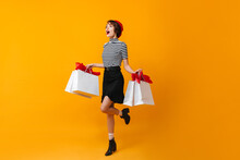 Full Length View Of Excited Slim Woman With Store Bags. Studio Shot Of Fashionable Shopaholic Girl.