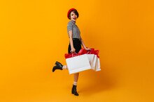 Smiling Shopaholic Girl Standing On One Leg. French Woman Posing With Store Bags On Yellow Background.