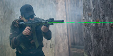 Army Soldier In Action Aiming At Weapon Laser Sight Optics. Shooting And Weapons. Outdoor Shooting Range