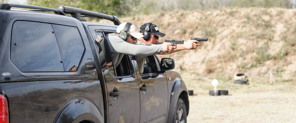 Fototapeta Military tactical car shooting. Army soldiers in action. Outdoor shooting range