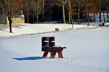 Empty Snow-covered Bench In The Winter At Nathaniel Cole Park In Harpursville In Broome County In Upstate NY.