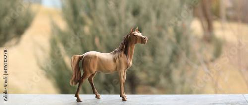 Fototapeta wooden figurine horse on nature background obraz