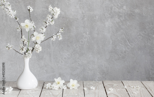 Photographie cherry flowers in white vase on background old gray wall
