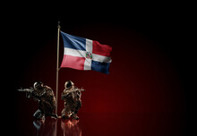 Concept Of Military Conflict. Waving National Flag Of Dominican Republic. Illustration Of Coup Idea. Two Soldier Statue Guards Defending The Symbol Of Country Against Red Wall