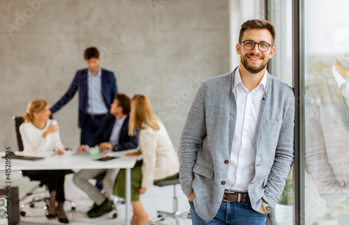 Handsome young business man standing confident in the office