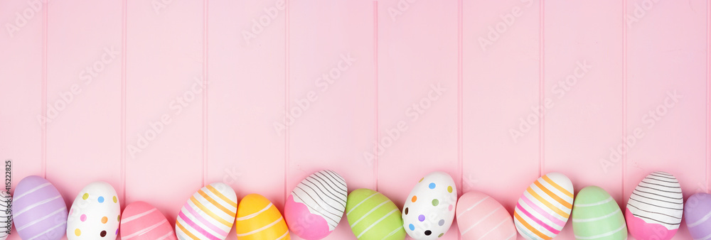 Fototapeta Colorful Easter Egg bottom border over a soft pink wood banner background. Top down view with copy space.