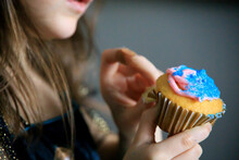 Little Girl Un-peeling A Cupcake With Pink And Blue Frosting