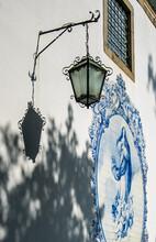 Típico Trabajo De Azulejos Portugués Dedicado A La Virgen María Con Tonalidades Azules, Sobre Una Fachada Blanca Con Un Farol Y Su Sombra, En Un Convento De Guimaraes, Portugal
