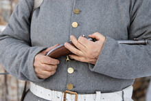 Male Hands Are Holding A Firearm - A Pistol From The Era Of The Napoleonic Wars. Historical Weapons, Antiques. Short-barreled Weapon.