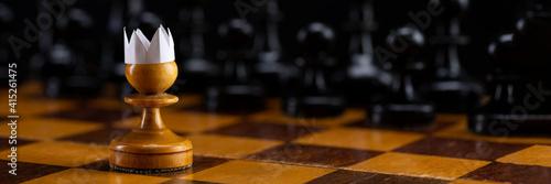 Billede på lærred Little brave pawn wearing artificial paper crown suit on chessboard with figures