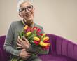 Senior female with flowers. International women's day. Senior female with short grey hair. Grandma with flowers. Happy and smiling senior lady. Celebrating valentines as a senior.