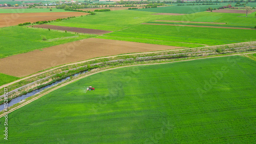 Fototapety, obrazy: Aerial view tractor spraying the chemicals on the large green fi