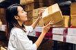 Leinwandbild Motiv Portrait of smiling asian manager worker woman standing and order details on cardboard box for checking goods and supplies on shelves with goods background in warehouse.logistic and business export