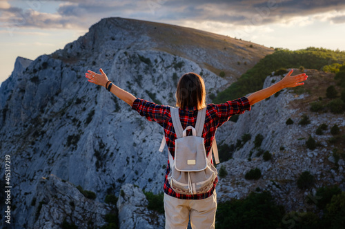 Fit female hiker with backpack standing on a rocky mountain ridge Fototapeta