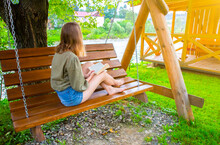 Hipster Girl Is Reading A Book On Wooden Bench. Woman Relaxing Outdoors On Porch Swing In The Nature. Cozy Photo. Summer Mood.