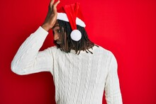 African American Man With Braids Wearing Christmas Hat Surprised With Hand On Head For Mistake, Remember Error. Forgot, Bad Memory Concept.