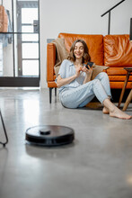 Black Robotic Vacuum Cleaner Cleaning The Floor While Woman Sitting Near Sofa And Using Phone. Smart Technology Concept. High Quality Photo