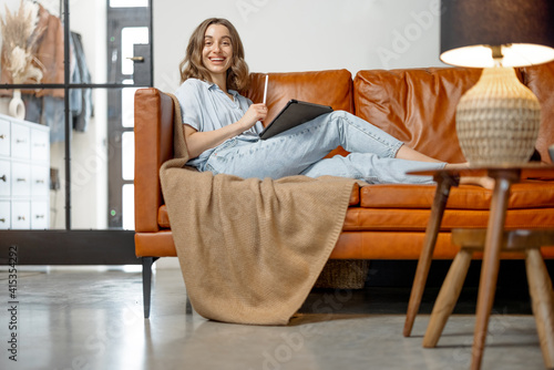 Obraz na plátně Beautiful woman working with digital tablet while sitting on foxy leather sofa in stylish interior design