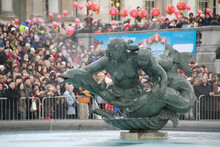 A Mermaid And Dolphin Statue In A Fountain With People Celebrating Chinese New Year At London's Trafalgar Square