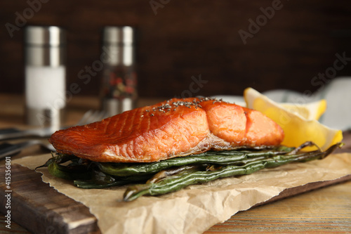 Fototapeta Tasty cooked salmon and vegetables served on wooden table. Healthy meals from air fryer obraz