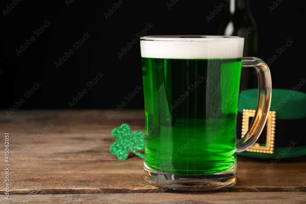 Fototapeta Green beer and St Patrick's Day decor on wooden table against black background. Space for text