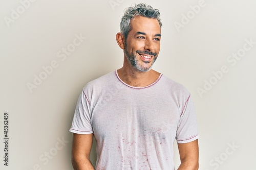 Canvas Print Middle age grey-haired man wearing casual clothes looking away to side with smile on face, natural expression