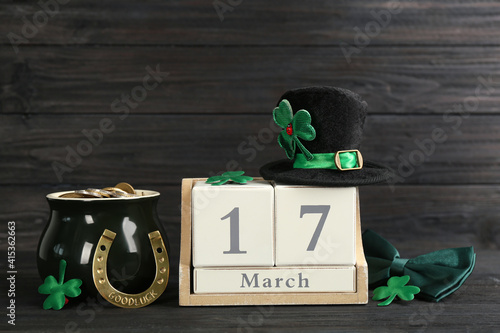 Fototapeta Leprechaun's hat, block calendar and St. Patrick's day decor on black wooden table obraz