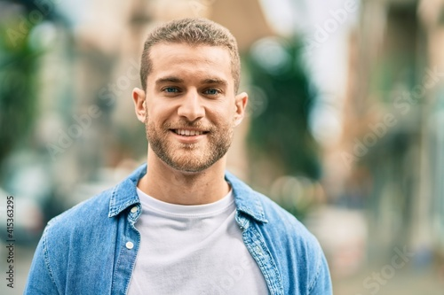 Young caucasian man smiling happy standing at the city. Fototapeta