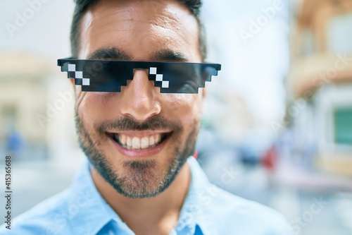Young hispanic man smiling happy wearing funny sunglasses standing at street of city.