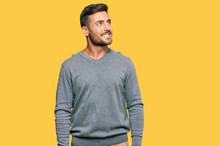 Handsome Hispanic Man Wearing Casual Clothes Looking Away To Side With Smile On Face, Natural Expression. Laughing Confident.