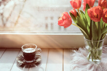 Oriental Coffee In Traditional Turkish Copper Coffee Pot With Flowers On Window Sill. Wooden Windowsill With Bunch Of Tulips Book. Cold Rainy Day In Spring. Cozy Scene, Hygge Concept.