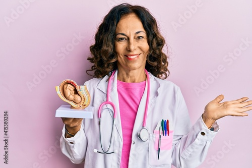 Fotografiet Middle age hispanic doctor woman holding anatomical model of female uterus with