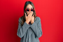 Young Brunette Woman Wearing Fashion And Modern Look Shocked Covering Mouth With Hands For Mistake. Secret Concept.