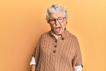 Senior Grey-haired Woman Wearing Casual Clothes And Glasses Winking Looking At The Camera With Sexy Expression, Cheerful And Happy Face.