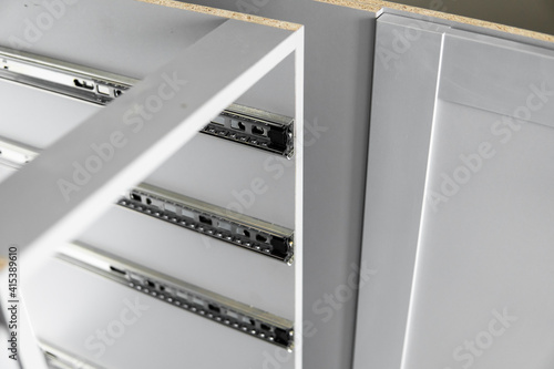 Foto Stainless telescopic bayonet drawer slide guides, installed on a kitchen cabinet from gray chipboard